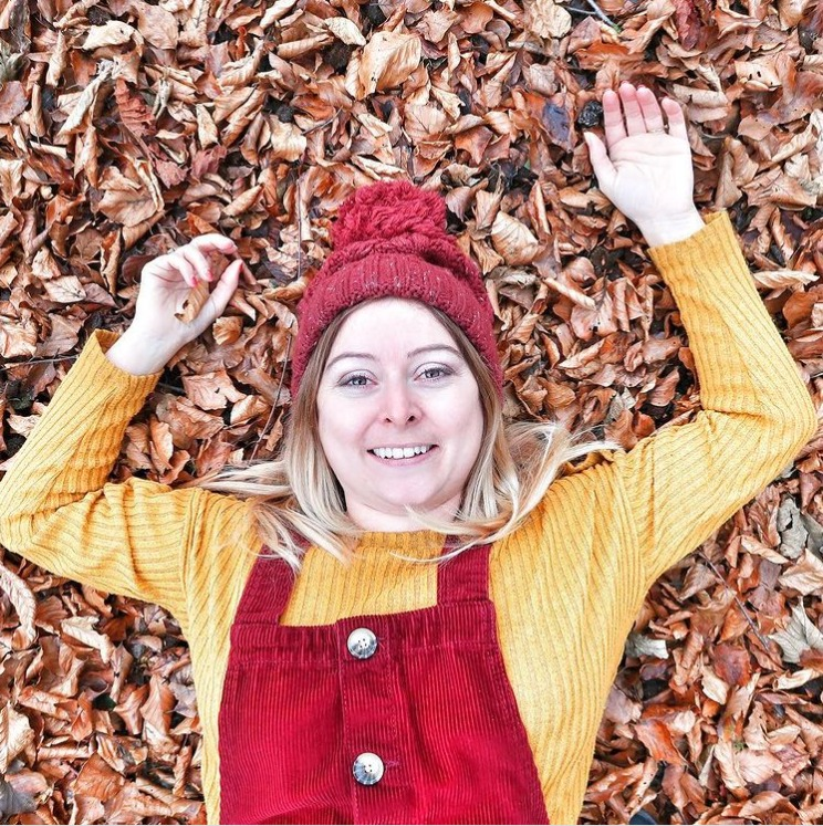 woman laid down in leaves autumn